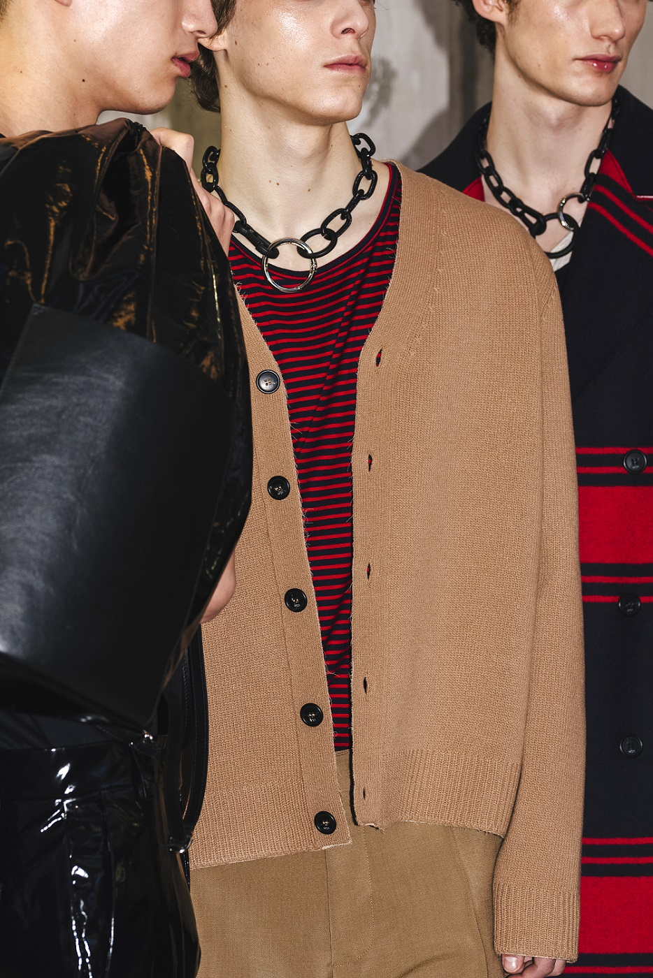 male model with brown cardigan and male model with black and red stripe jacket